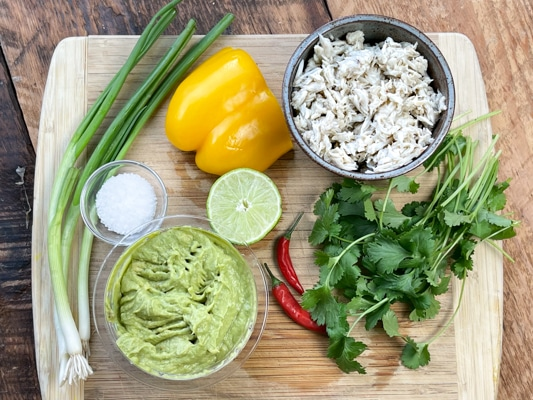 Ingredients for spicy crab wonton cups with guacamole on a wooden cutting board.