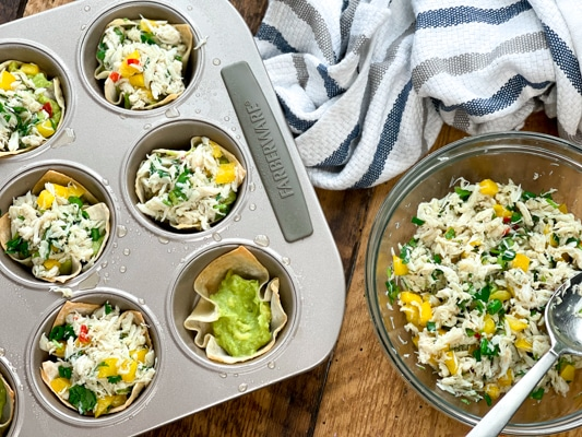 An aluminum muffin tray filled with baked wontons filled with crab salad and guacamole and a clear glass bowl with crab salad on the side on top of a wooden board. on a wooden board.