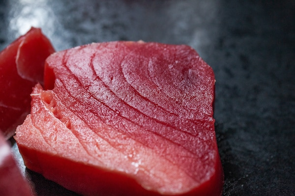 a raw tuna steak on top of a black board