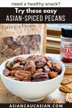 A white bowl filled with golden toasted spiced pecans on a wooden boards with a bag of pecans and sriracha seasoning behind it and loose pecans on the board.