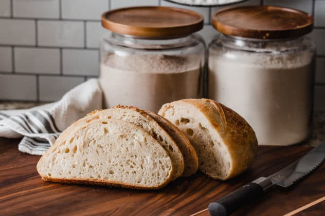 A sliced loaf of sour dough bread on a wooden board with a bread knife along side and flour canisters behind.
