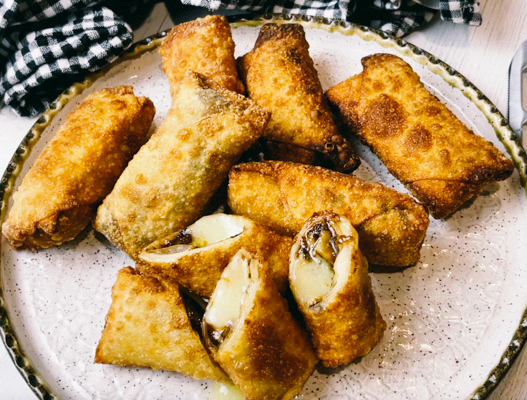 Crispy, golden spring rolls filled with brie and fig on a round white serving platter.