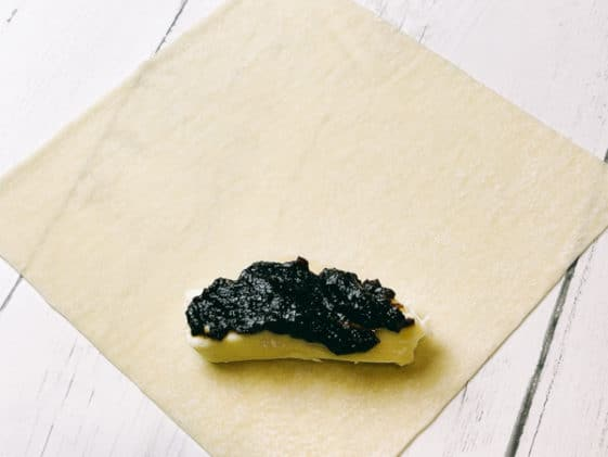 A wonton wrapper on a white board with a piece of brie and fig jam on top ready to be assembled.