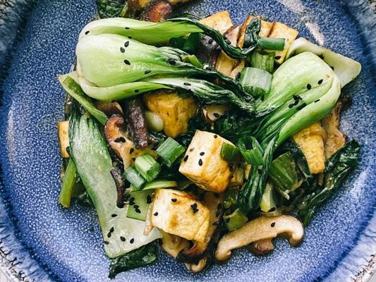 Stir-fry miso shiitake mushrooms, tofu, and baby bok choy on a blue plate.