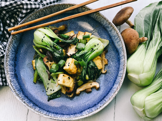 Stir-fry miso shiitake mushrooms, tofu, and baby bok choy on a blue plate with wooden chopsticks, and fresh baby bok choy and shiitake mushrooms on the side.
