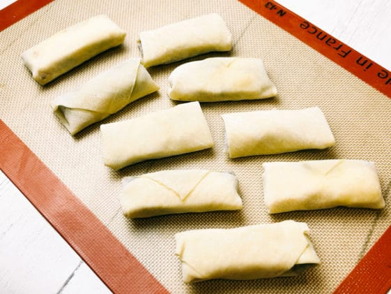 Two rows of uncooked spring rolls on a silicone mat.