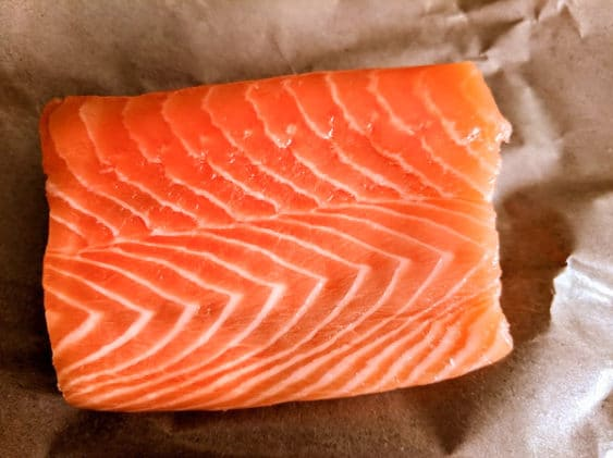 perfect marbled sushi-grade filet of salmon on a piece of brown parchment paper