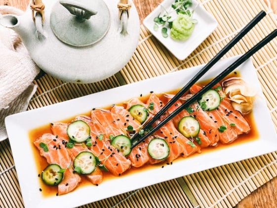 Slices of fresh sashimi salmon on a white platter with sliced cucumbers on top and sprinkles of black sesame seeds, with black chopsticks, a Japanese tea kettle, and a small white bowl of green wasabi on the side.