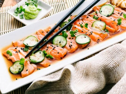 Slices of fresh sashimi salmon on a white platter with sliced cucumbers on top and sprinkles of black sesame seeds, with black chopsticks and a small white bowl of green wasabi on the side.
