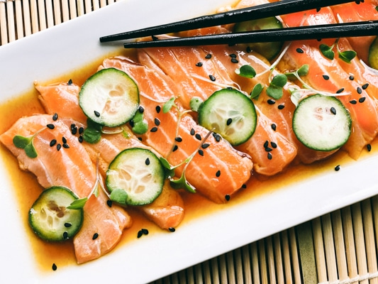 Slices of fresh sashimi salmon on a white platter with sliced cucumbers on top and sprinkles of black sesame seeds, with black chopsticks.