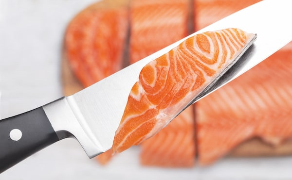 Raw fresh salmon fillet cut into slices and a piece on a chef's knife.