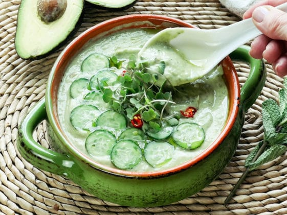 A woman's hand holding a white spoon inside a green bowl filled with cucumber avocado soup, with sliced avocados on the side.