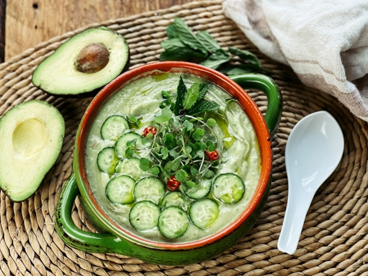 A bowl filled with spicy cucumber avocado soup topped with sliced cucumbers and herbs with a sliced avocado and a white spoon on the side.
