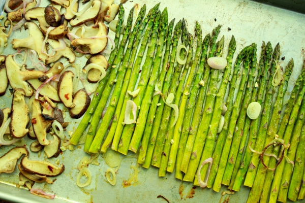 Roasted asparagus and shiitake mushrooms on a baking tray topped with shallot rings.