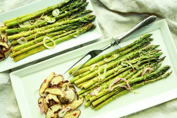 Roasted asparagus and shiitake mushrooms on two white trays with a serving fork on the side.