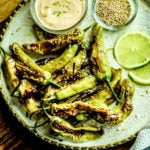Blistered shishito peppers on a white plate with lime wedges, aioli dipping sauce, and sesame seeds on the side.