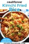 A bowl of Kimchi cauliflower fried rice with chopsticks and blue and white napkin on the side