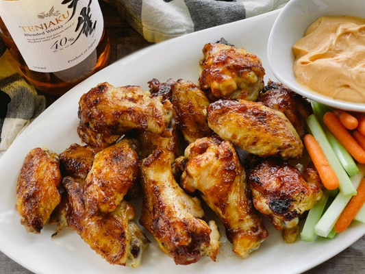 A bottle of Japanese whiskey placed behind a white plate of saucy chicken wings, celery and carrot sticks, and a bowl of aioli dip.