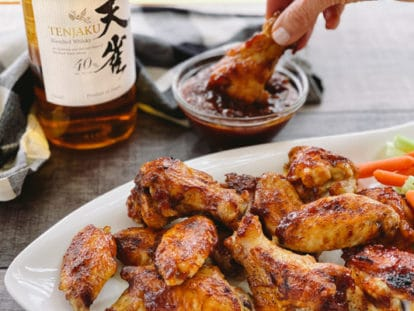 A woman's hand dipping a chicken wing drum into sauce next to a bottle of Japanese whiskey, and a white plate of chicken wings in front.