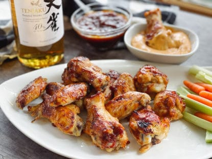 A bottle of Japanese whiskey placed behind a white plate of saucy chicken wings, celery and carrot sticks, with a bowl of aioli dip and extra sauce behind.