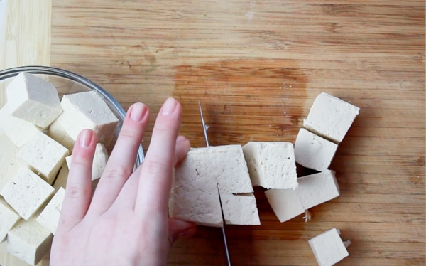 A woman cubing raw tofu on a wooden board.