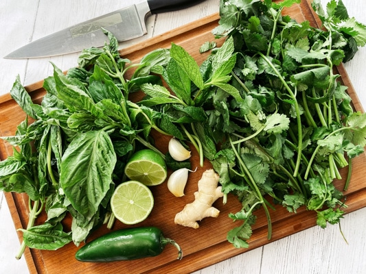 Fresh basil, cilantro, mint, and cilantro leaves on top of a wooden cutting board, along with a jalapeno pepper, fresh lime halves, and garlic cloves.