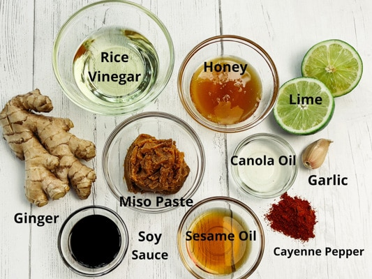 Labeled ingredients for miso ginger dressing on top of a white board.