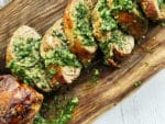 Thick slices of pork tenderloin on a rustic wooden board topped with a vibrant green cilantro, mint, basil sauce.