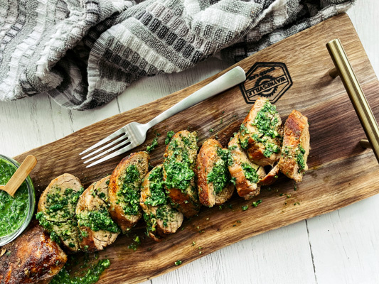 Thick slices of pork tenderloin on a rustic wooden board topped with a vibrant green cilantro, mint, basil sauce and a small bowl of sauce and a fork on the side.