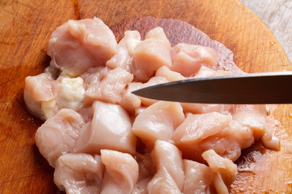 Fresh chicken cubes on a wooden cutting board with a kitchen knife.