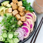A black bowl filled with miso tofu poke bowl ingredients and white rice, with chopsticks and clear jar of miso ginger dressing on the side.