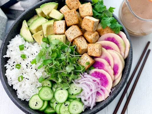 A black bowl filled with miso tofu poke bowl ingredients and white rice, with chopsticks and a clear jar of miso ginger dressing on the side.