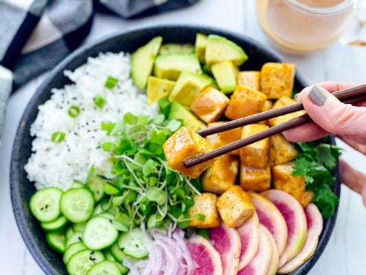 A woman holding chopsticks with a tofu cube, and a miso tofu poke bowl underneath.