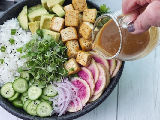 A miso tofu poke bowl in a black vessel with a woman pouring miso ginger dressing on top.