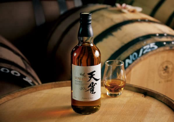 A bottle of Tenjaku whiskey from Japan on top of a wooden whiskey barrel with other barrels behind it.