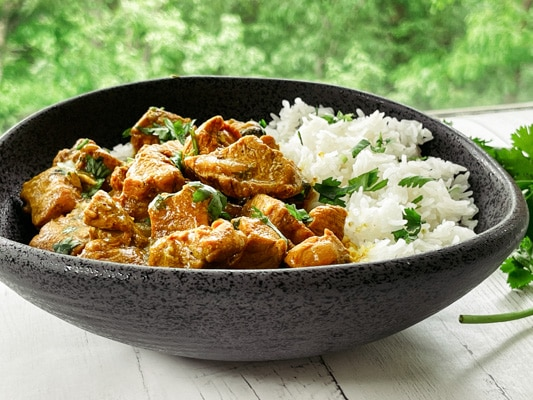 A black bowl of Thai curry chicken with white rice and fresh cilantro on the side, on top of a white board.