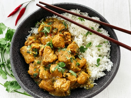 A black bowl of Thai curry chicken with white rice and chopsticks with fresh cilantro and red chili peppers on the side, on top of a white board.