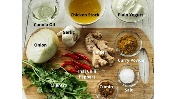 Ingredients for making Thai Curry Chicken on a wooden cutting board.
