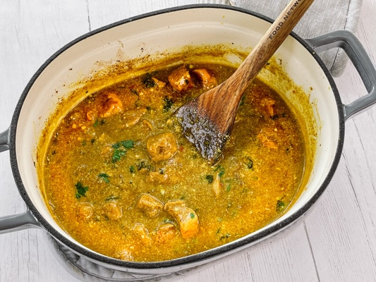 Thai Curry Chicken in a large gray pot with a wooden spatula inserted, on top of a white surface.