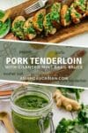 Thick slices of pork tenderloin on a rustic wooden board topped with a vibrant green cilantro, mint, basil sauce and a small bowl of sauce and a fork and herb sauce on the side.