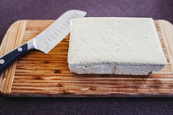 A block of extra firm tofu on wooden cutting board with a chef's knife