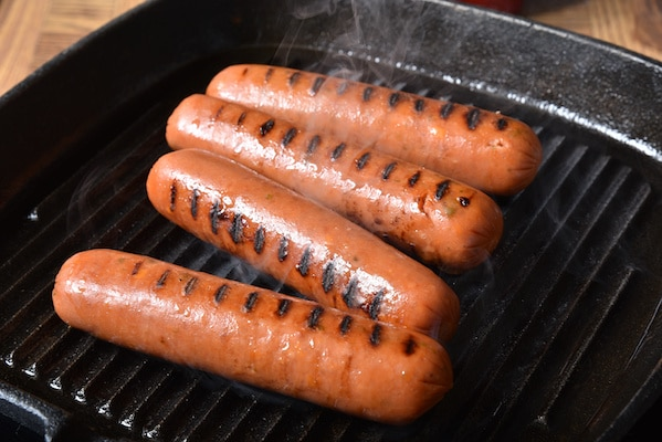 Grilling four hot dogs on a cast iron grill