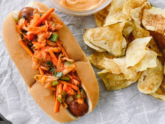 A hot dog in a bun topped with kimchi slaw with potato chips and aioli on the side.