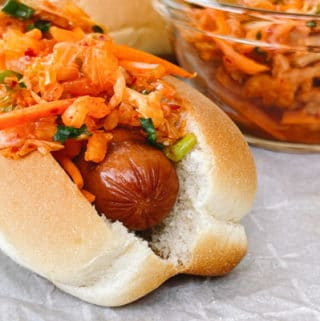 Close up of a hot dog in a bun topped with kimchi slaw with extra slaw on the side in a clear glass bowl.