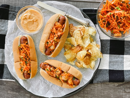 Three hot dogs in buns topped with kimchi slaw with potato chips, extra slaw and aioli on the side on top of a checkered napkin.