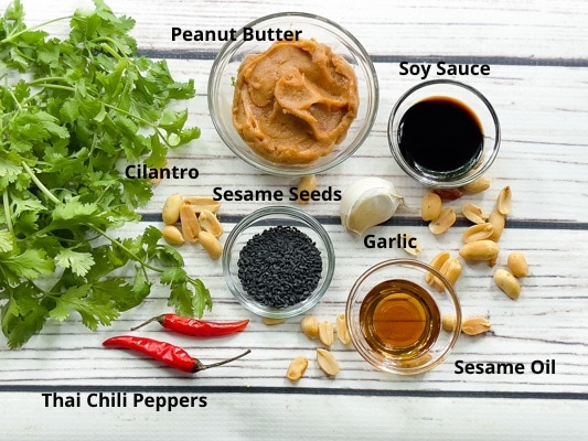 Ingredients for making spicy peanut dressing on top of a white board.