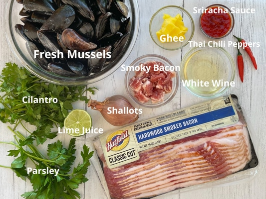 Ingredients for steamed mussels on a white board including a package of Hatfield hardwood smoked bacon, fresh green herbs, shallots, fresh mussels in a bowl, cut bacon, white wine, ghee, Thai chili peppers, and sriracha sauce.