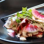 A vibrant mushroom and radish salad in a black bowl with sprouts on top and silver chopsticks on the side