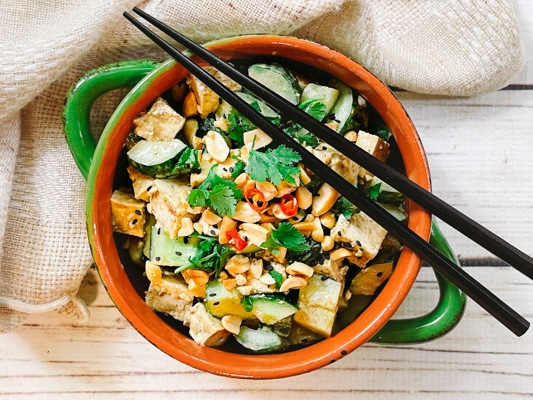 A green bowl filled with a vibrant spicy Asian tofu salad with cucumbers, cilantro, and peanuts, and black chopsticks on top.