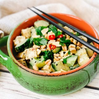 A green bowl filled with a vibrant spicy Asian tofu salad with cucumbers, cilantro and peanuts, and black chopsticks on top.
